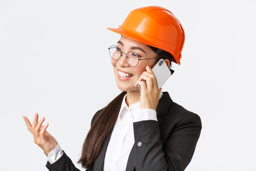 Close-up of professional smiling asian female entrepreneur at factory, chief engineer in safety helmet and suit, talking on phone, having business conversation with investors of enterprise
